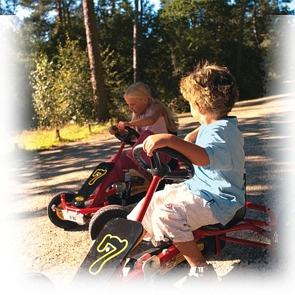 two kids on go cart style bicycle