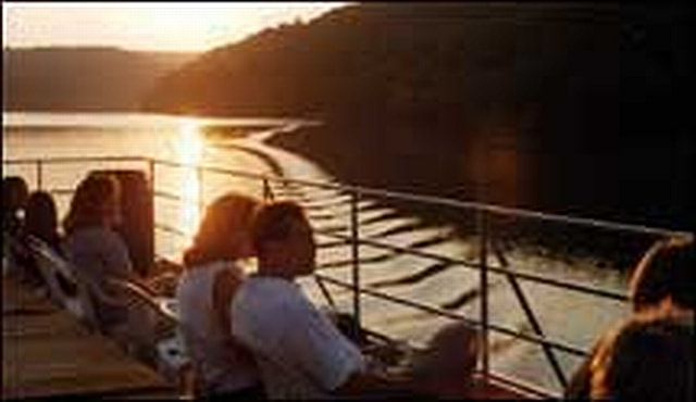 Couple on the top deck of the riverboat during sunset cruise